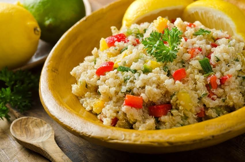 A healthy delicious quinoa salad with lemon, lime, red pepper, yellow pepper, green onion, and parsley.